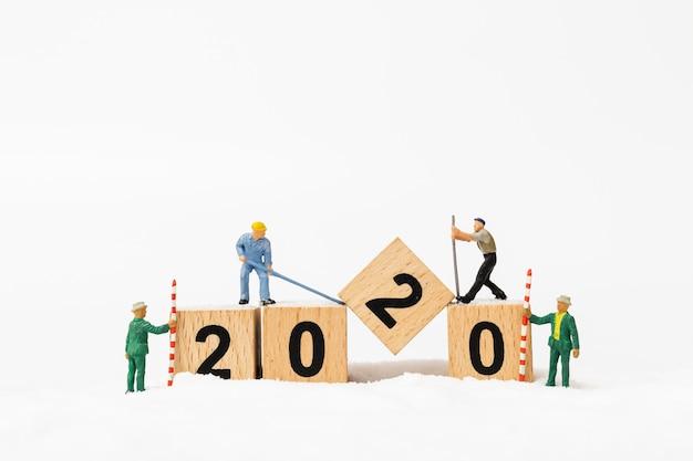 Miniature people, worker team create wooden block number 2020 Premium Photo