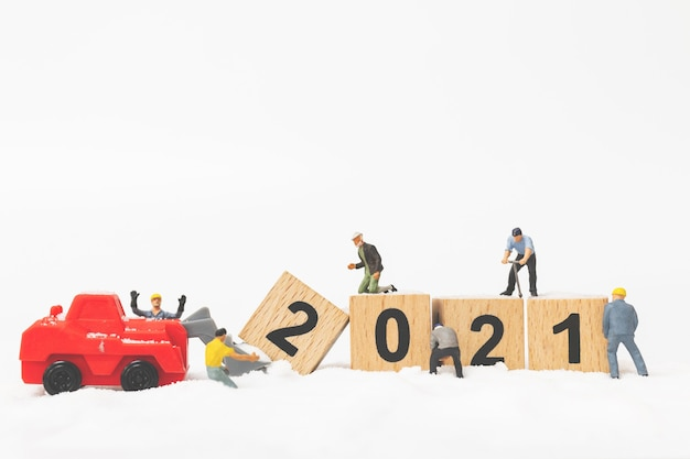 Miniature people : worker team create wooden block number 2021, happy new year concept Premium Photo