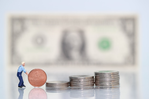 Miniature people: worker with coins, business concept using as background Premium Photo