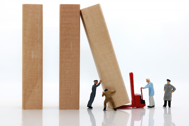 Miniature people: workers team stopping the domino effect. Premium Photo