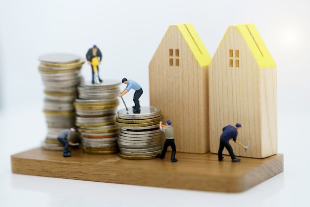 Miniature people: workers working with tools on coins stack with wood house. Premium Photo