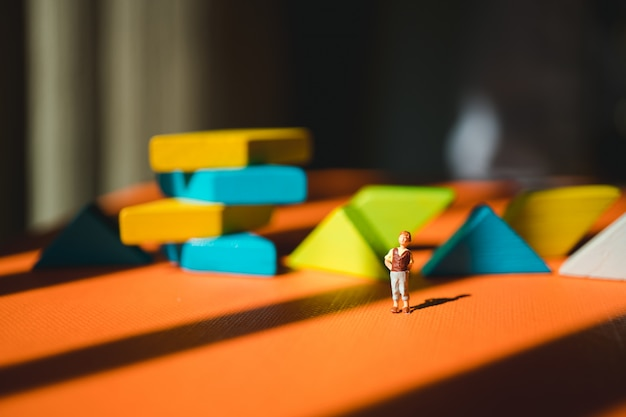 Miniature people, young boy standing on tangram puzzle background using as education skill concept Premium Photo
