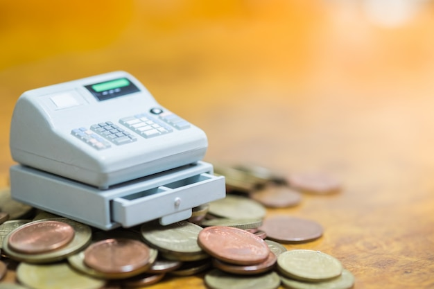 Miniature point of sale cashier machine on pile of coins Premium Photo