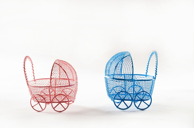 Miniature prams on a white background close-up. baby and pregnancy concept and copy space. Premium Photo