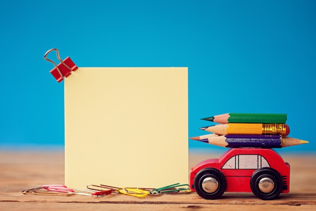 Miniature red car carrying a colorful pencils on blue Premium Photo
