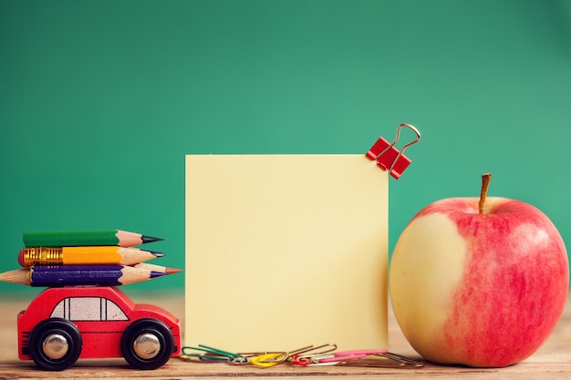 Miniature red car carrying a colorful pencils and red apple on wooden table and place for text Premium Photo
