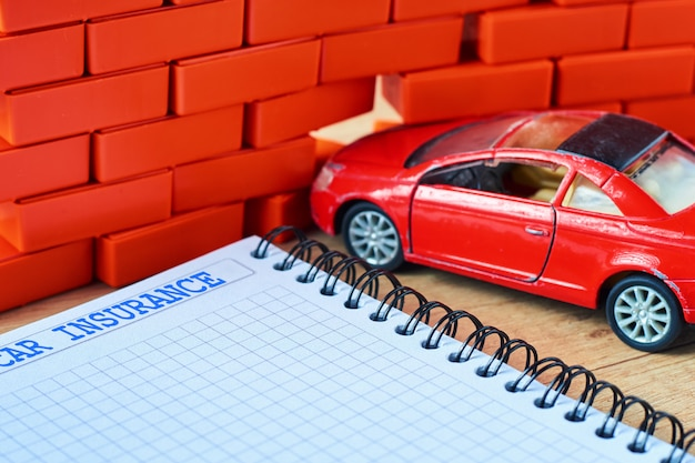 Miniature red car crashed in a brick wall and car insurance form Premium Photo