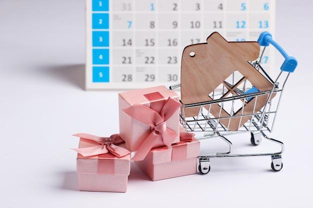 ミニチュアショッピングカート、家の図、白い背景の上のデスクトップカレンダーとギフトボックス。ホリデーショッピング、ブラックフライデー、毎月の特別オファーのコンセプト。住宅購入 Premium写真