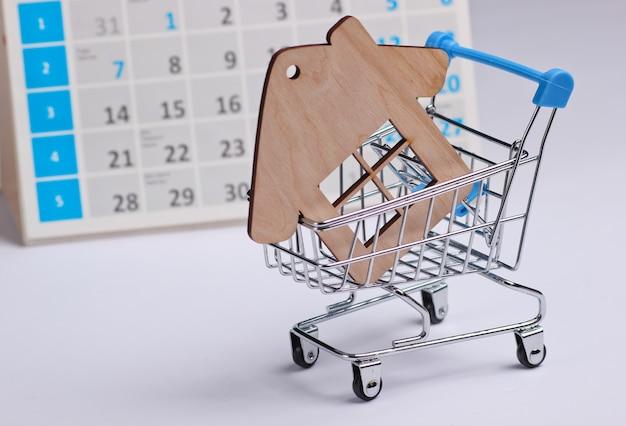 ミニチュアショッピングカート、白い背景の上のデスクトップカレンダーと家の図。ホリデーショッピング、ブラックフライデー、毎月の特別オファーのコンセプト。住宅購入 Premium写真