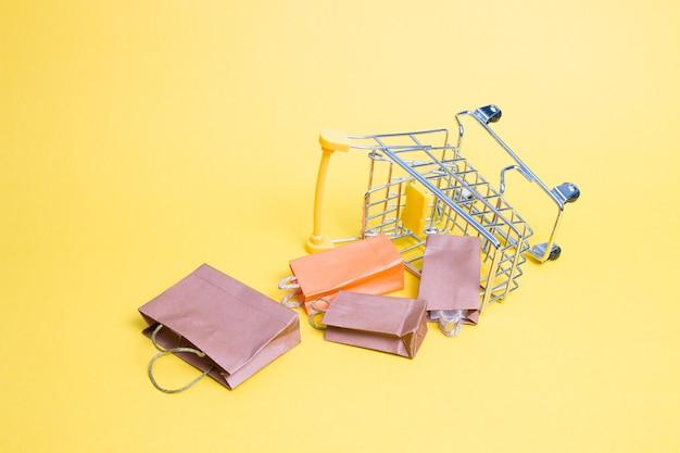 노란색 바탕에 미니어처 쇼핑 트롤리 프리미엄 사진