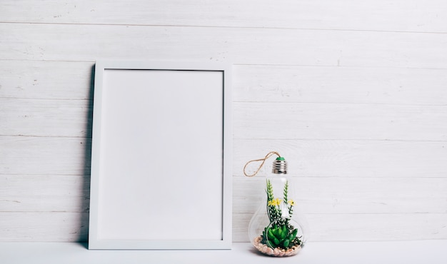 Miniature succulent plant inside glass hang lamp near the white frame against wooden wall Free Photo
