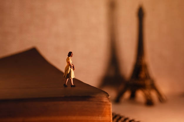 Miniature tourist woman standingon the aged book and looking at the eiffel tower. Premium Photo