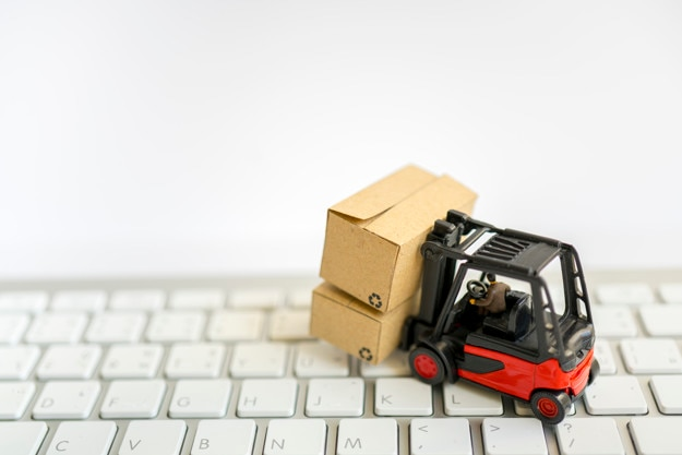Miniature toy:Fork lift operator during lift product box Premium Photo