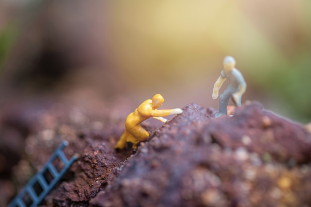 Miniature of two friends helping each other to reach the top of the mountains Premium Photo