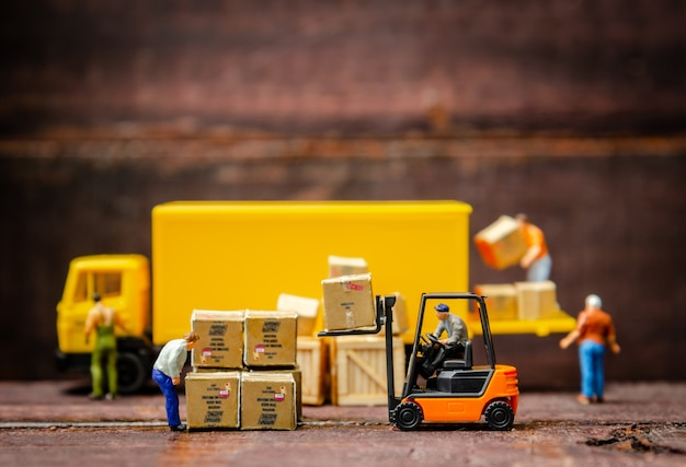 Miniature warehouse workers forklift carrying goods box to semi truck with trailer Premium Photo