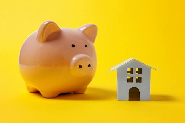 Miniature white toy house and piggy bank on yellow background Premium Photo