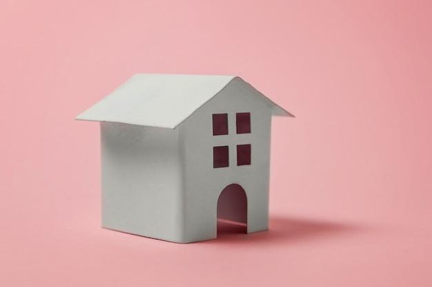 Miniature white toy house on pink background Premium Photo