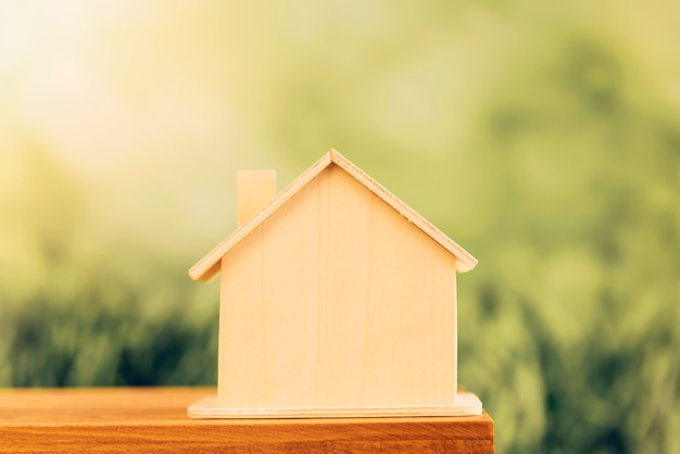 Miniature wooden house on table against blur green background Free Photo