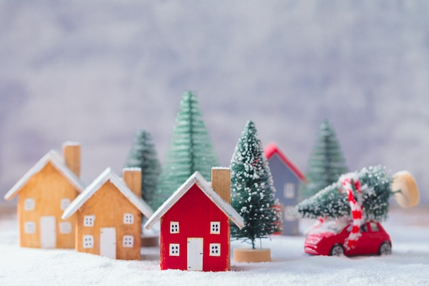 Miniature wooden houses and small red car with fir tree on the snow over blurred christmas decoration Premium Photo
