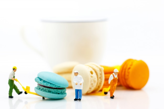 Miniature worker move macaron with cup of coffee. Premium Photo