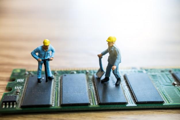 Miniature worker repairing circuit motherboard Premium Photo