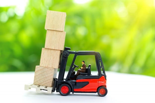 Miniature worker transporting wooden block. Premium Photo
