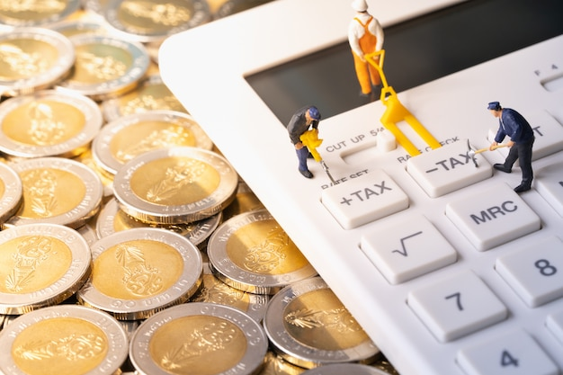 Miniature workers digging tax button on calculator on pile of coins Premium Photo