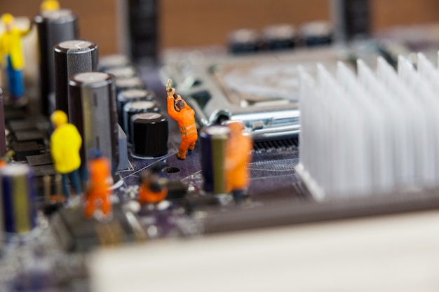 Miniature workers working on chip of motherboard Free Photo