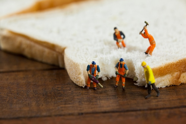 Miniature workers working on sliced of bread Free Photo