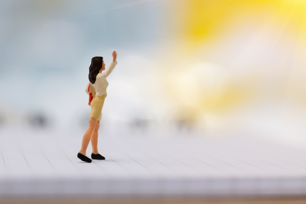 Miniature working woman walking on book using as , business . Premium Photo