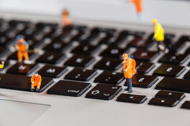 Miniature workmen repairing a laptop keyboard Free Photo