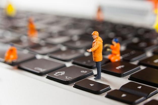 Miniature workmen repairing a laptop keyboard Free Photo
