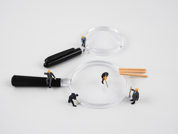 The miniature works on a magnifying glass and the background is white Premium Photo