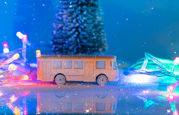 Miniature yellow bus and fir tree during snowfall, imitation of night time with garland Premium Photo