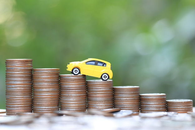 Miniature yellow car model on growing stack of coins money on nature Premium Photo