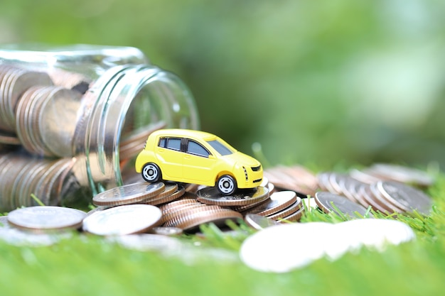 Miniature yellow car model on stack of coins money in glass bottle on nature green background Premium Photo