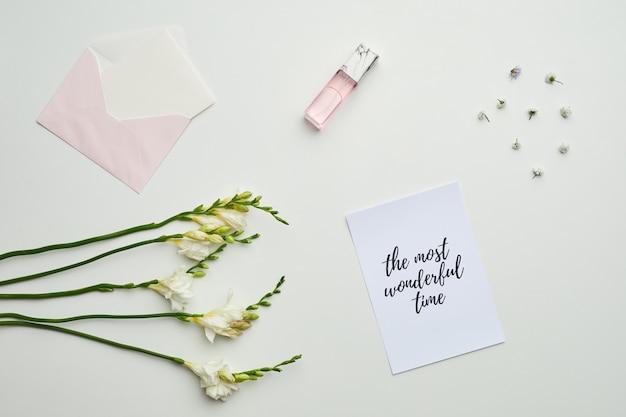 花のディテールと最も素晴らしい時間をレタリングするテーブル上の封筒と香水の最小限の背景構成、 Premium写真