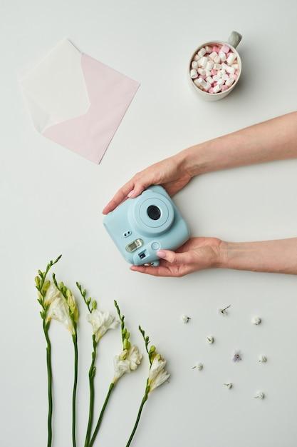 花のアクセントとココアのカップとテーブルの背景の間にインスタントカメラを保持している女性の手の最小限の背景構成、 Premium写真