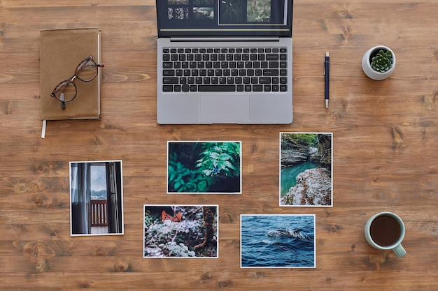 Minimal background composition of printed photographs and laptop on textured wooden desk, photographers office, copy space Premium Photo