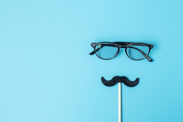 青の背景に最小限の黒い口ひげと眼鏡。幸せな父の日と国際男性デーの概念 Premium写真