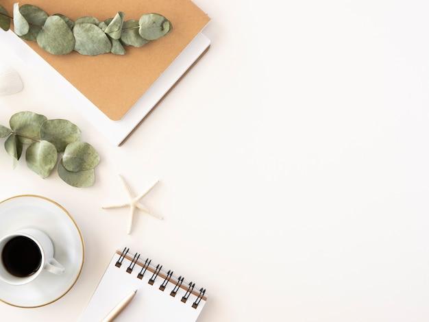 Минимальное рабочее пространство блоггера с блокнотом, буфером обмена, кофе и веткой эвкалипта Premium Фотографии