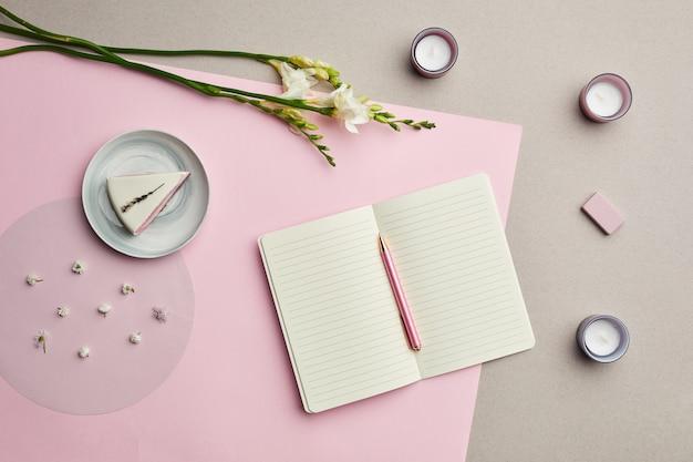 花の装飾が施されたピンクのグラフィック背景上の空白のプランナーの最小限の構成、 Premium写真