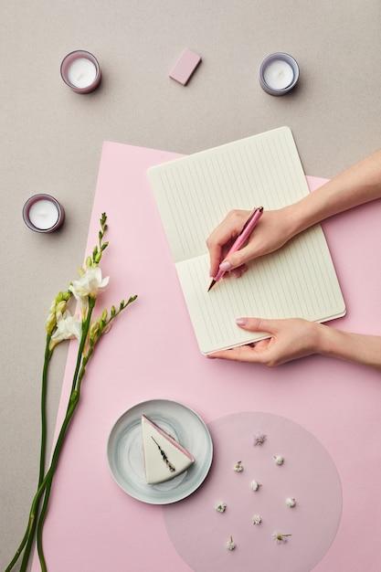 花の装飾が施されたピンクのグラフィックの背景の上に空白のプランナーで書く女性の手の最小限の構成、 Premium写真