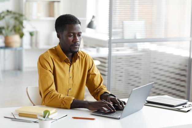 사무실에서 흰색 책상에 앉아있는 동안 노트북을 사용하는 현대 아프리카 계 미국인 남자의 최소 초상화, 복사 공간 프리미엄 사진