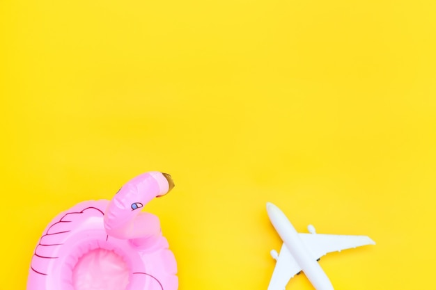 Minimal simple flat lay with plane and inflatable flamingo isolated on yellow Premium Photo