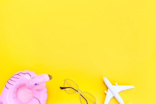 Minimal simple flat lay with plane sunglasses and inflatable flamingo isolated on yellow Premium Photo