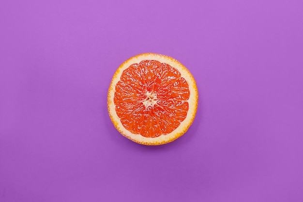 Minimal style, creative layout orange and grapefruit on purple background Premium Photo