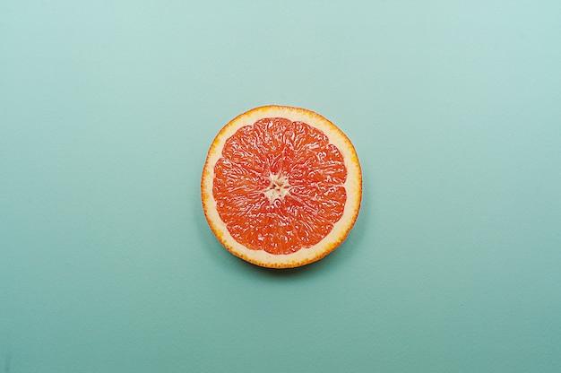 Minimal style, creative layout orange and grapefruit  on turquoise background Premium Photo