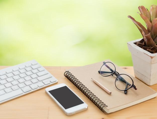 Минимальное рабочее пространство с клавиатурой, смартфоном, очками, блокнотом и карандашом на деревянном столе Premium Фотографии