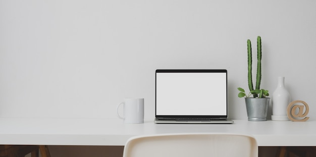 Minimal workspace with open laptop computer and decorations on white table and white wall Premium Photo